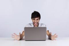 Jonge mens die aan laptop schreeuwt Stock Foto's