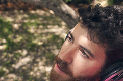 Jonge mens die aan muziek in het bos luisteren Royalty-vrije Stock Foto