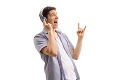 Jonge mens die aan muziek luisteren en het gebaar van de rotshand maken Royalty-vrije Stock Foto