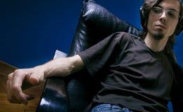 Jonge mens die aan muziek luistert Stock Afbeelding