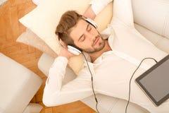 Jonge mens die aan muziek luistert Stock Foto