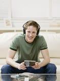 Jonge mens die aan muziek op hoofdtelefoons luistert Royalty-vrije Stock Afbeeldingen