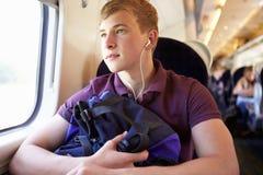 Jonge Mens die aan Muziek op Treinreis luisteren Stock Afbeeldingen