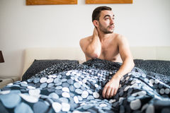 Jonge mens die aan neckache in slaapkamer thuis lijden royalty-vrije stock afbeelding