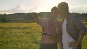 Jonge mens die aan oude landbouwer verklaren en tablet houden, die zich op mooi tarwegebied tijdens gelukkige zonsondergang bevin stock video