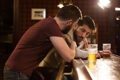 Jonge mens die aan zijn dronken vriend spreken royalty-vrije stock foto