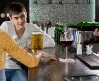 Jonge mens die aan zijn meisje bij de bar babbelt Royalty-vrije Stock Foto