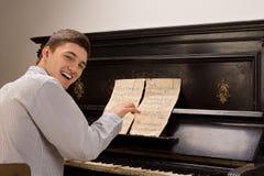 Jonge mens die aangezien hij het spelen van de piano zit lacht royalty-vrije stock afbeeldingen