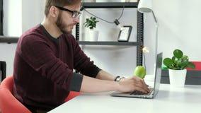 Jonge mens die in alleen bureau en het glimlachen 4k werken stock footage