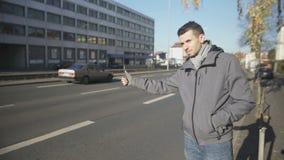 Jonge mens die auto in onbekende stad, het goedkope reizen, lift halen stock video