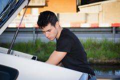 Jonge mens die bagage en zak nemen uit autoboomstam Royalty-vrije Stock Afbeeldingen