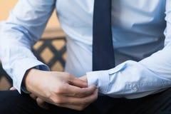 Jonge mens die in bedrijfsbureauoverhemd zijn kokerknopen dichtknopen Stock Foto