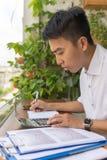 Jonge mens die berekening op calculator doen stock afbeelding