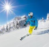 Jonge mens die bergaf in Alpen ski?en Stock Afbeeldingen