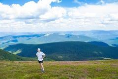 Jonge mens die bij de Bergentribunes van de Karpaten wandelen bovenop een heuvel Stock Foto's