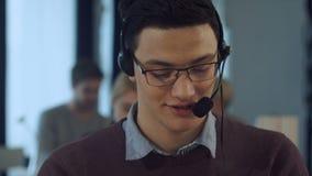Jonge mens die bij een computer in call centre het glimlachen werken stock video