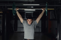 Jonge mens die bij gymnastiek een barbell opheffen Royalty-vrije Stock Fotografie