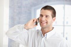 Jonge mens die bij het mobiele telefoon glimlachen spreekt Royalty-vrije Stock Foto