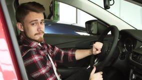 Jonge mens die binnenland van een nieuwe auto onderzoeken bij de het handel drijvensalon royalty-vrije stock foto's