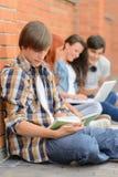 Jonge mens die boekvrienden op achtergrond bestuderen stock fotografie