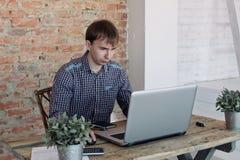 Jonge mens die in bureau werken, zittend bij bureau, het schrijven Stock Foto's