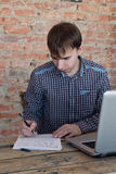 Jonge mens die in bureau werken, zittend bij bureau, het schrijven Stock Fotografie