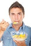 Jonge mens die cornflakesgraangewassen eet Royalty-vrije Stock Afbeeldingen