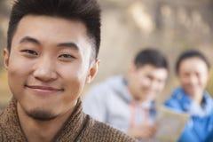 Jonge mens die de camera, vrienden bekijken die de kaart op de achtergrond, portret bekijken royalty-vrije stock afbeelding