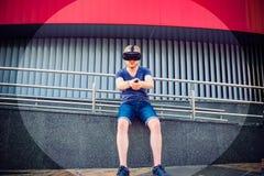 Jonge mens die de controlebordknoop drukken die van virtuele werkelijkheidsglazen of 3d bril op de stedelijke de bouwachtergrond  Stock Foto