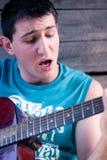 Jonge mens die de gitaar speelt Stock Afbeelding