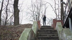 Jonge mens die de jeugd verspillen terwijl het drinken van alcohol, die in verlaten park wandelen stock videobeelden