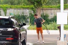 Jonge mens die de kant van zijn auto met water bespuiten royalty-vrije stock afbeelding
