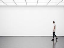 Jonge mens die in de lege galerij lopen stock afbeelding