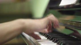 Jonge mens die de piano spelen De handen sluiten omhoog oefeningen op het muzikale instrument Toetsenbord muzikaal instrument sal stock footage