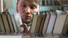 Jonge mens die de rekken van boeken in a doorbladeren stock video