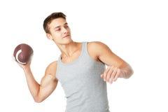 Jonge mens die de rugbybal werpen Royalty-vrije Stock Afbeeldingen