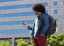 Jonge mens die in de stad met cellphone lopen Royalty-vrije Stock Foto's