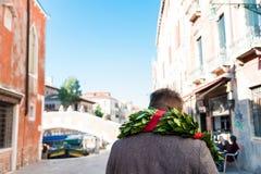 Jonge mens die de straten van Venetië na graduatieceremonie lopen met traditionele laurierkroon bij de universiteit van Venetië royalty-vrije stock fotografie
