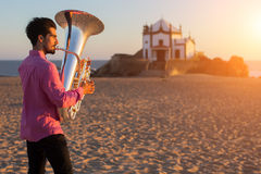 Jonge mens die de trompet op het van de overzeese instrument kusttuba spelen stock afbeeldingen