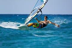 Jonge mens die de wind in plonsen van water surft Stock Foto's