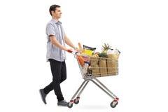 Jonge mens die die een boodschappenwagentje duwen met kruidenierswinkels wordt gevuld Royalty-vrije Stock Foto's