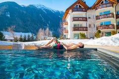 Jonge mens die door de open pool in het midden van de bergen in Alpen liggen Royalty-vrije Stock Foto's