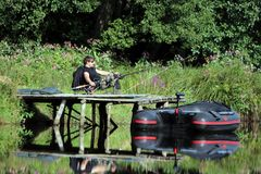 Jonge mens die door de rivier vissen Royalty-vrije Stock Afbeeldingen