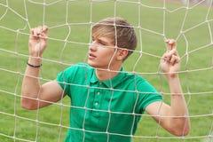 Jonge mens die door netto het doelvangst van de voetbalvoetbal kijken royalty-vrije stock afbeeldingen