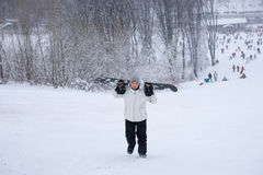 Jonge mens die door sneeuw met zijn snowboard ploeteren Stock Foto