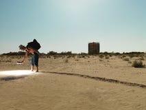Jonge mens die door zand met licht zoekt Royalty-vrije Stock Afbeeldingen