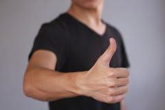 Jonge mens die duim toont Geïsoleerdu op grijze achtergrond Stock Fotografie