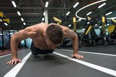 Jonge mens die duw UPS in gymnastiek doen royalty-vrije stock afbeeldingen