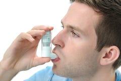 Jonge mens die een astmainhaleertoestel met behulp van Stock Afbeeldingen