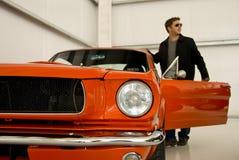 Jonge Mens die in een Auto van de Mustang krijgt Stock Foto's
